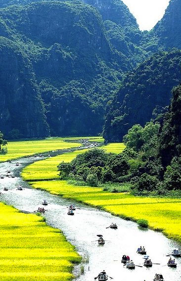 Fleuve, champ verdoyant entre les montagnes