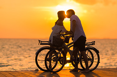 Couple à vélo s'embrassant devant le coucher de soleil