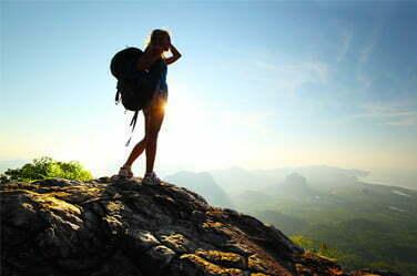 Randonneuse faisant une pause en haut d'un rocher