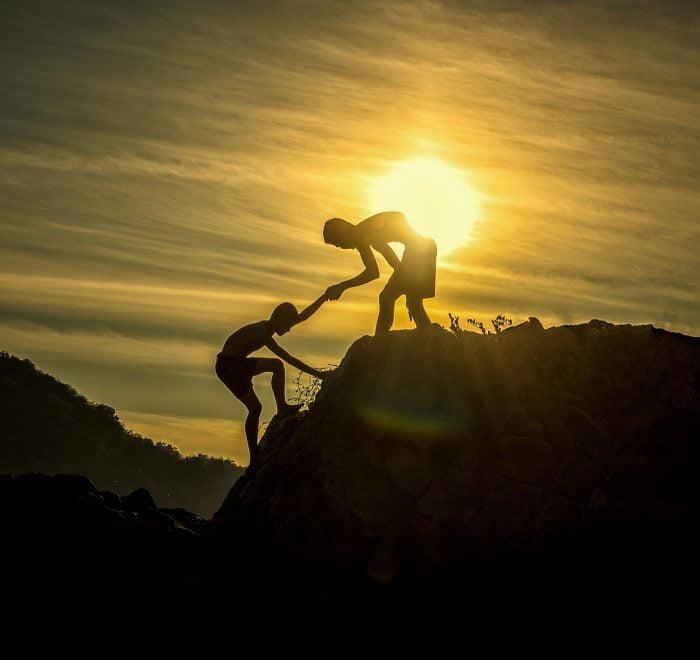 Deux amis escaladant un rocher