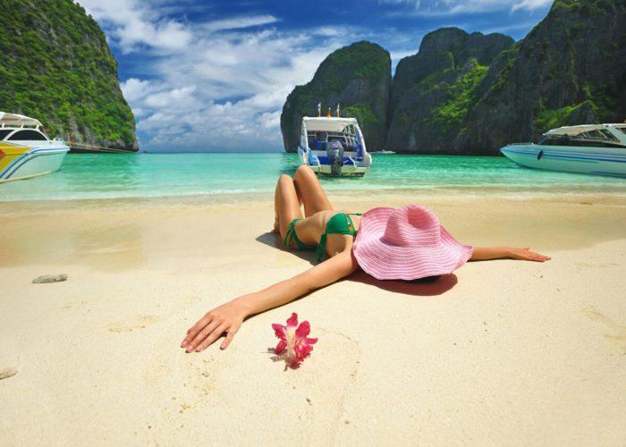 Femme alongée sur une plage de sable fin face à une eau turquoise