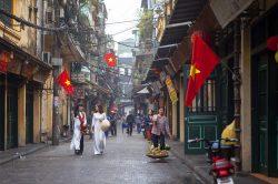 Rue à Hanoi avec des vendeuses de fruits et des femmes en tenues traditionnelles