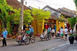 Touristes en Tuk-Tuk dans les rues d'Hoi An