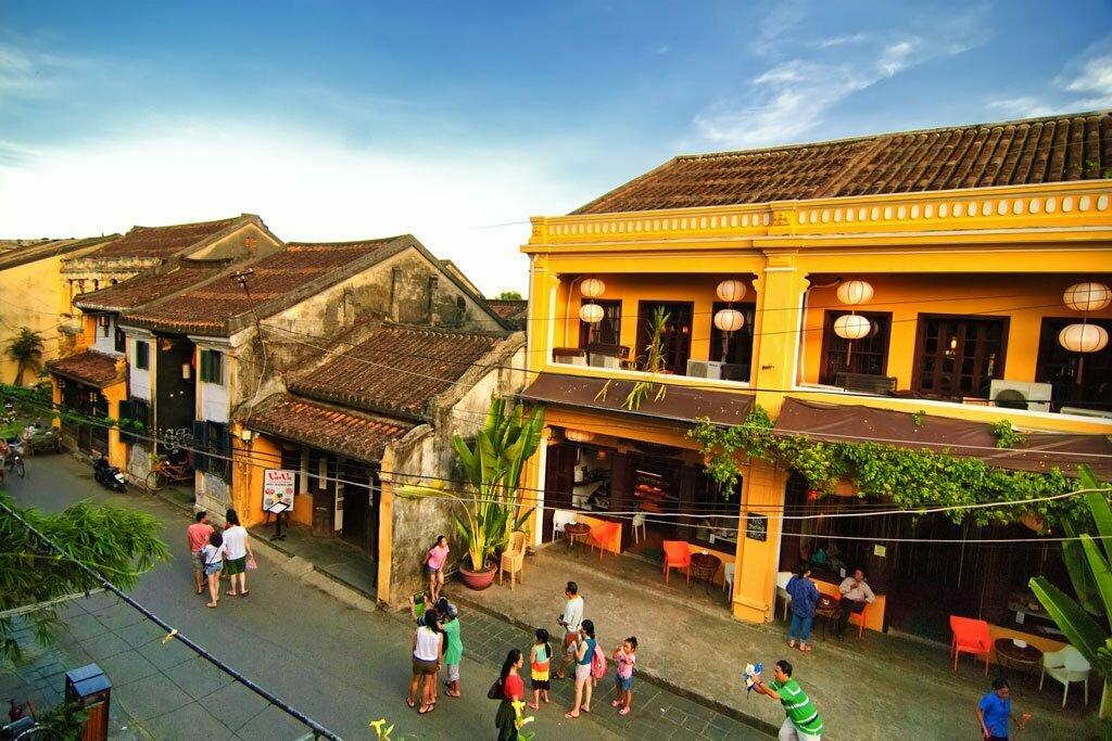 Rue colorée et passants prenant des photos à Hoi An