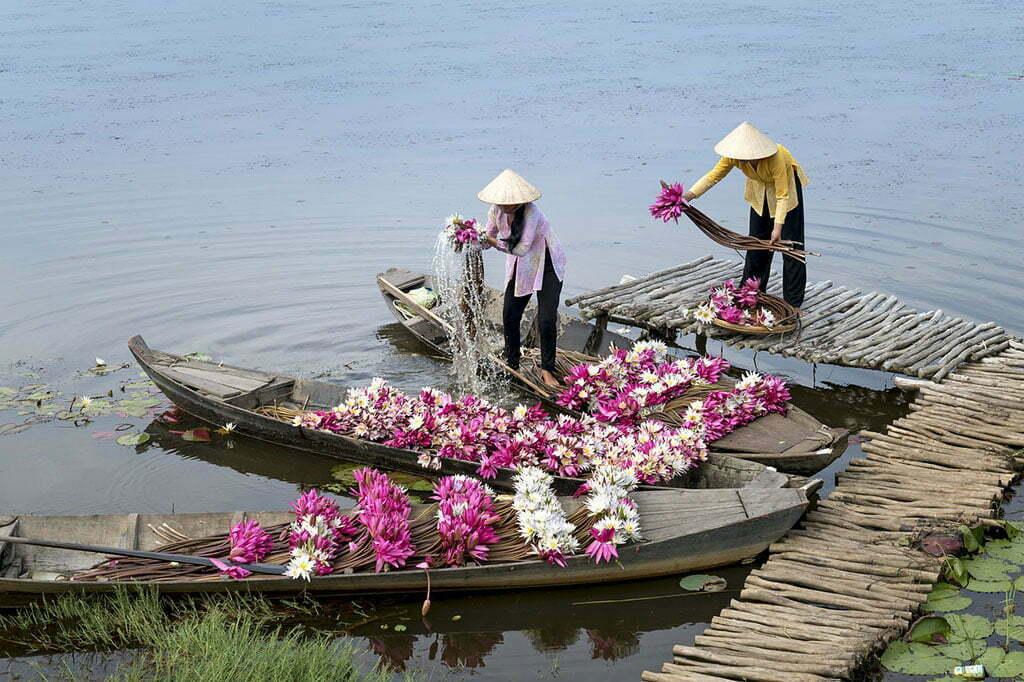 Vendeuses de fleurs préparant leurs barques sur le Mékong
