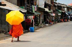 Moine tenant un parapluie et marchant dans la rue