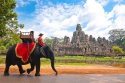 Touristes sur un éléphant et temple en pierre à Siem Reap