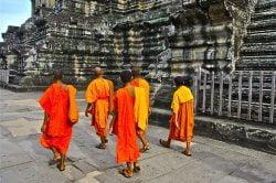Moines marchant autour d'un temple en pierre à Siem Reap