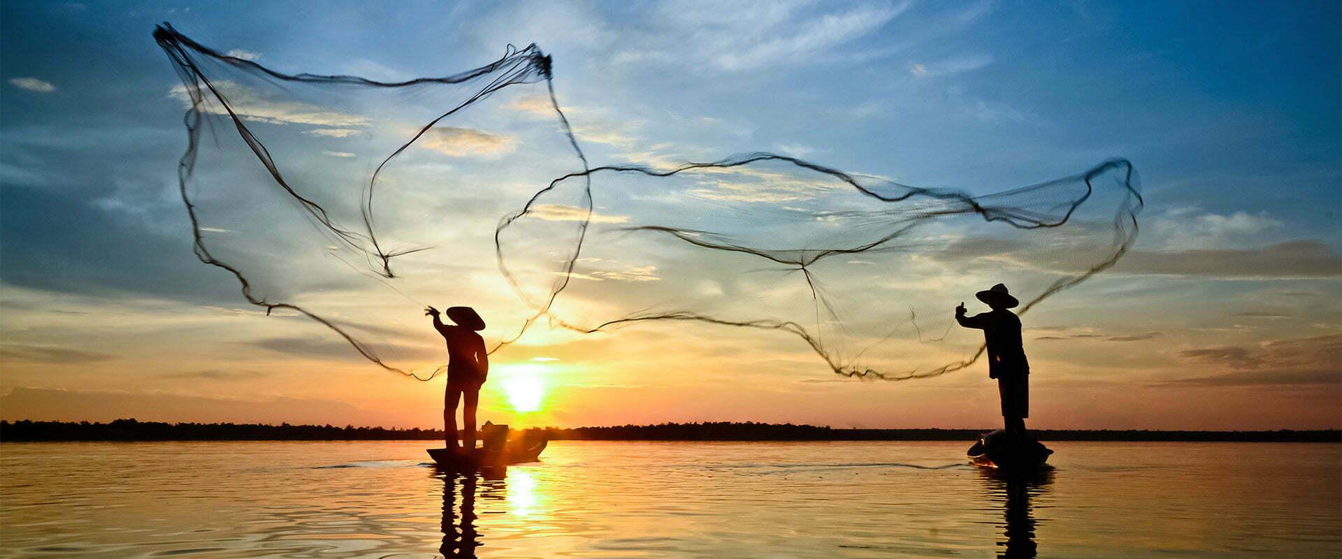 Pêcheurs lançant leurs filets au lever du soleil