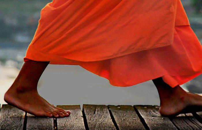 moine bouddhiste marchant sur un pont Laos