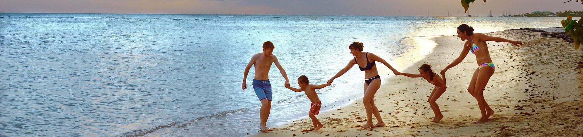 Famille se tenant la main sur la plage