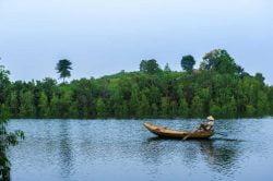 Un homme guidant sa barque sur le fleuve tranquille de Thac Ba