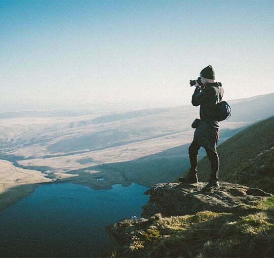 Photographe en haut d'une montagne prenant une photo de la vallée