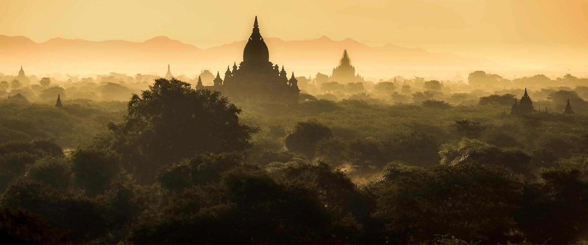 Aube sur un temple entouré d'une forêt en Birmanie