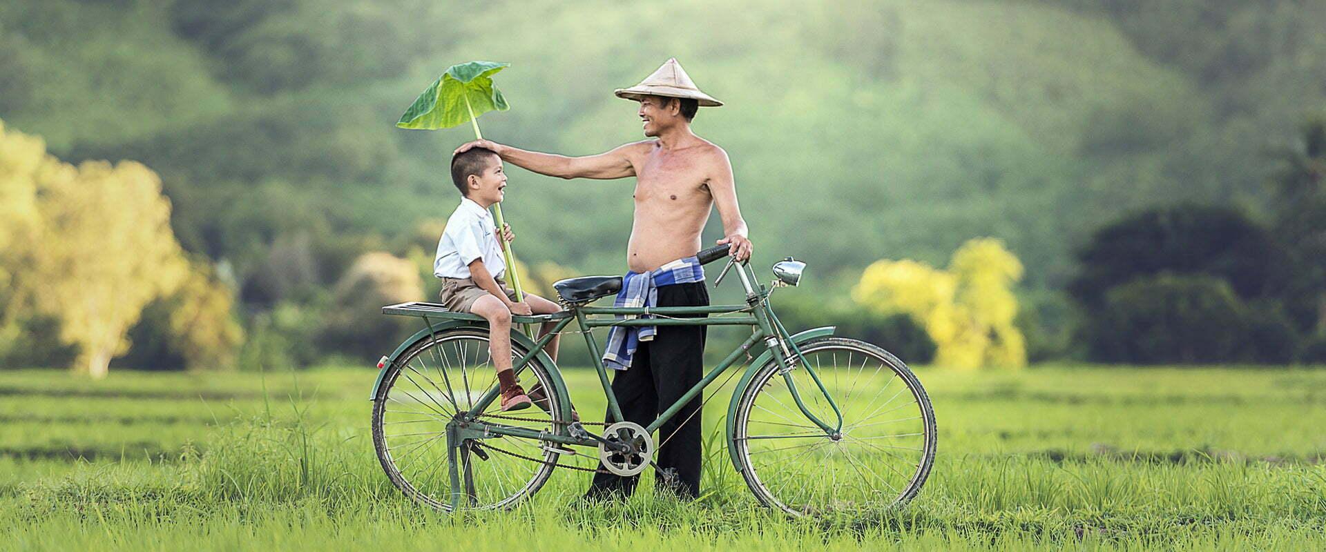 père et son fils à vélo dans la campagne, Cambodge