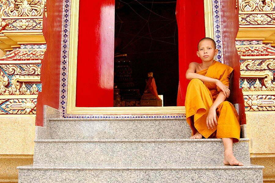 battambang cambodge, enfant moine assis sur les marches d'un temple