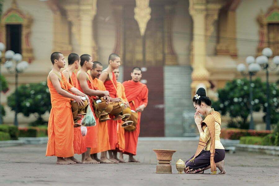 femme priant devant les moines au Cambodge
