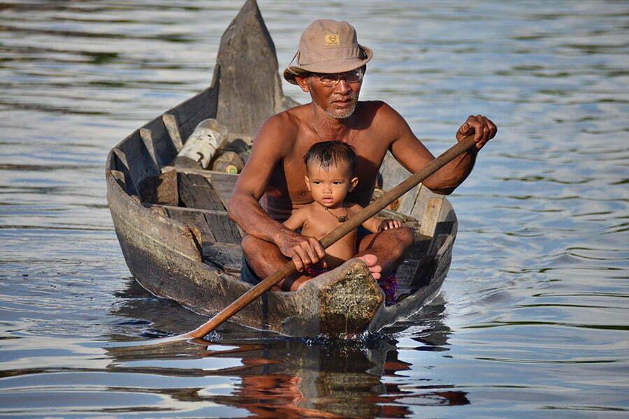 père et son fils en barque sur tonle sap cambodge