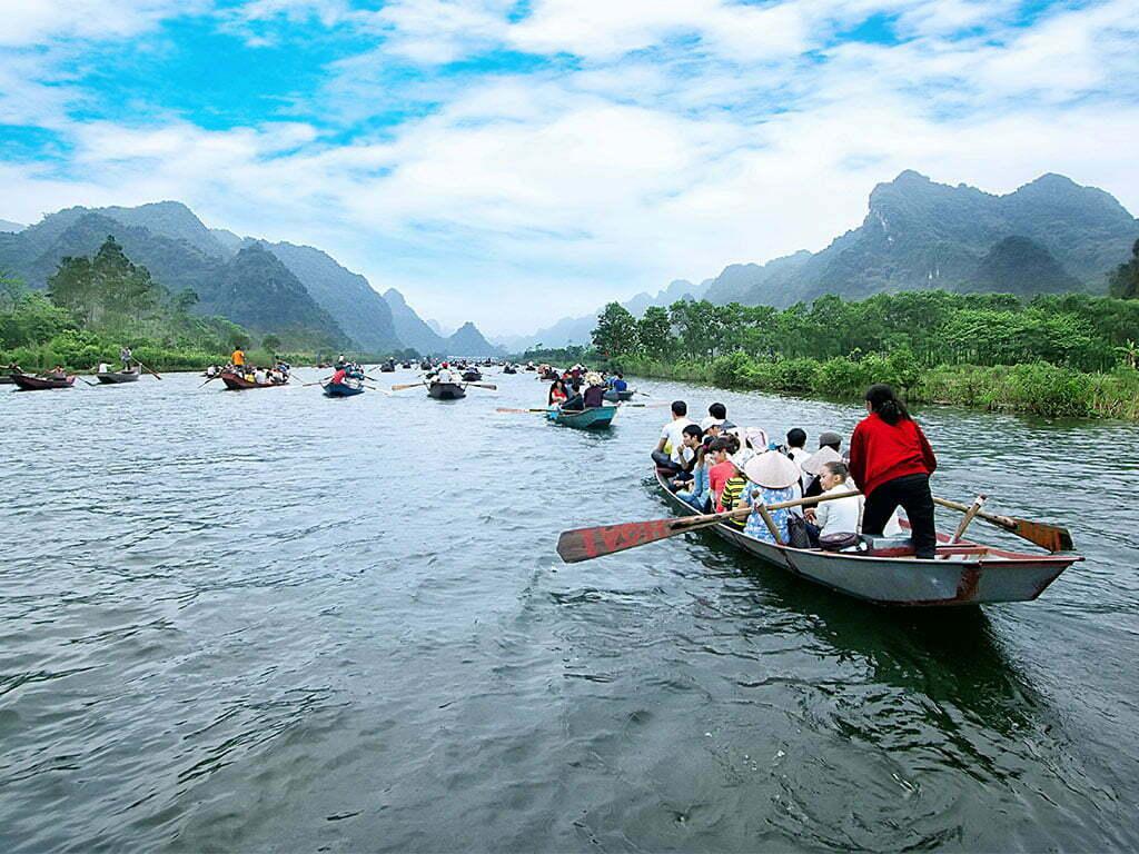 Barques et touristes vogant entre les montagnes de Ninh Binh