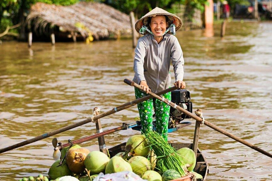femme sur barque transportant des noix de coco mekong