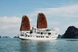 Jonque blanche avec voiles marrons dans la baie d'Halong