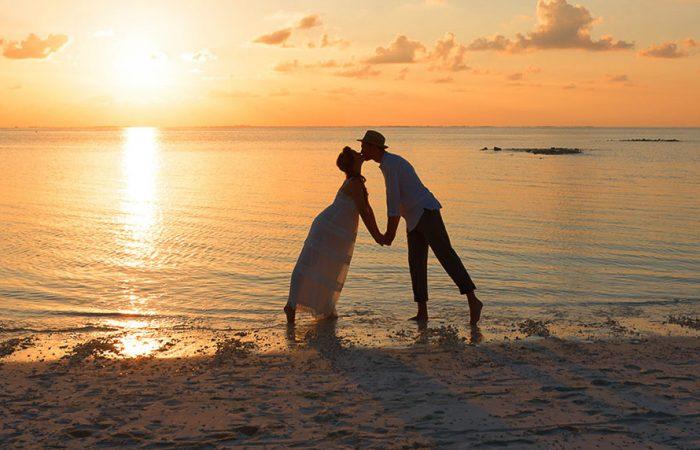 Couple s'embrassant sur la plage pendant le coucher de soleil