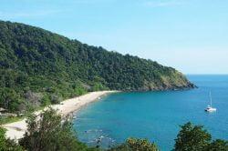 Plage de sable blanc, mer turquoise et montagne à Koh Lanta