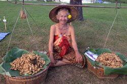 Femme en habits traditionnels vendant des fruits